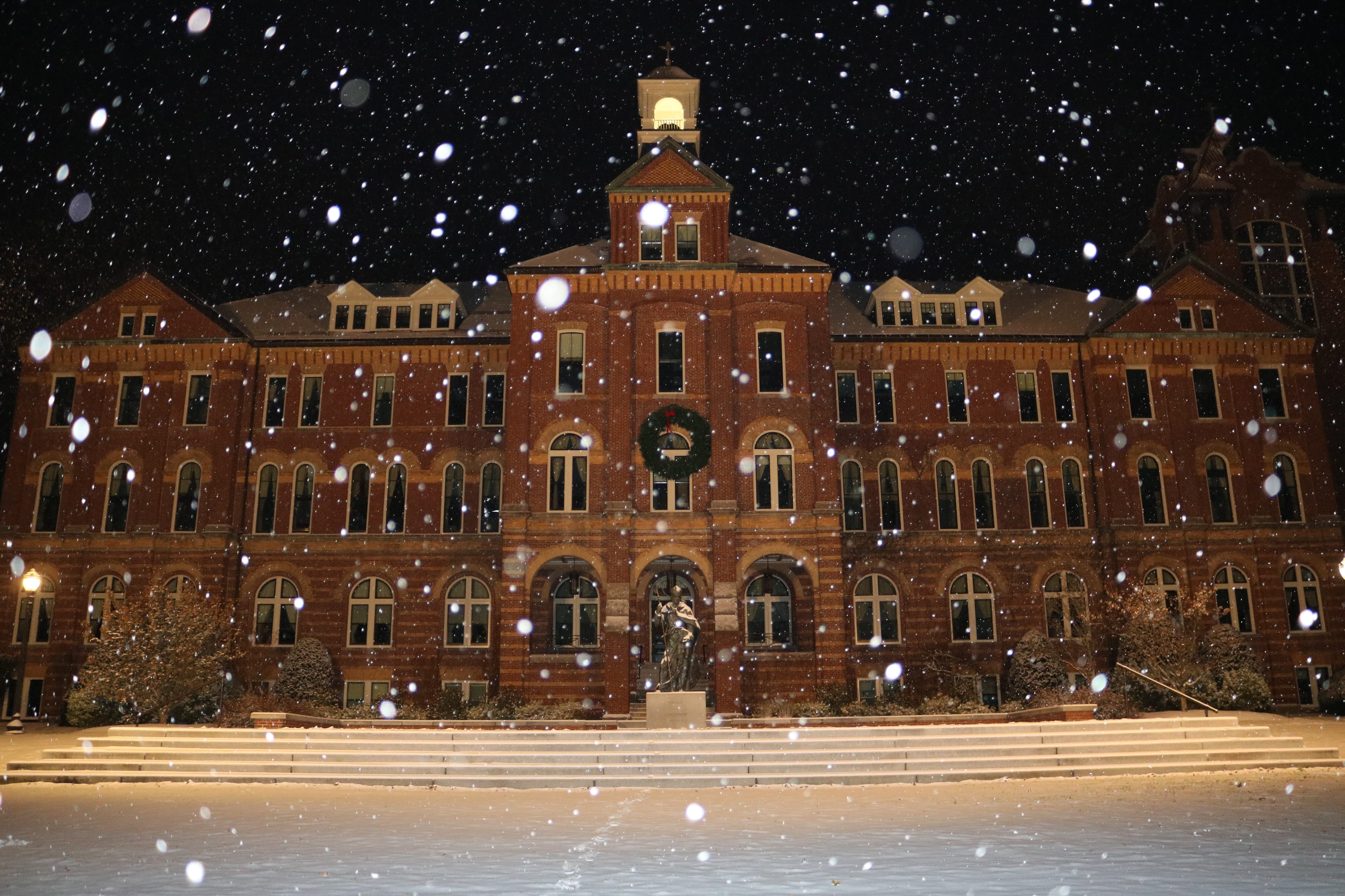 Snow falls at night on Alumni Hall