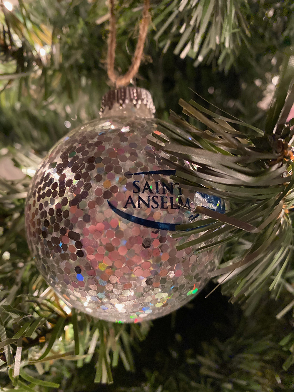 Saint Anselm College Holiday Ornament hangs on a pine tree