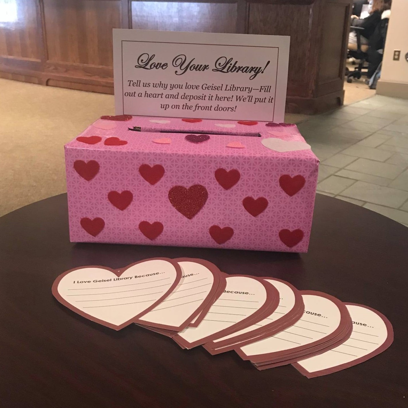 "Photo of heart-covered drop box and paper hearts saying ""I love Geisel Library because..."""