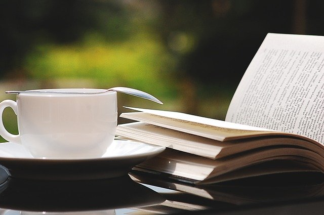 open book next to teacup sitting outside
