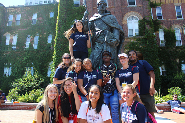 Intercultural Center students with the statue of Saint Anselm