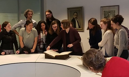 Students gather around a table to learn from an old book