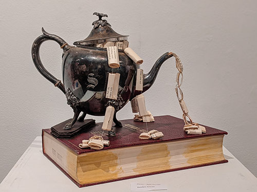 tea kettle with book pages pouring out