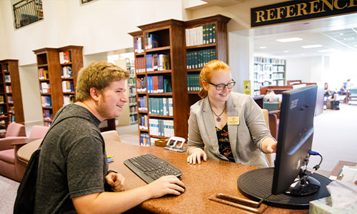student and staff at the reference desk