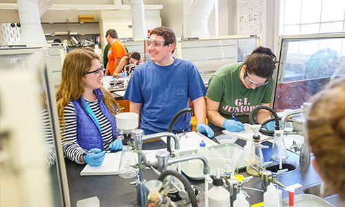 students talking while working on a lab